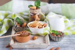 Miel en el cuenco, el muesli, las hojas de menta, las almendras y el tarro con leche en la bandeja de madera Fotografía de archivo