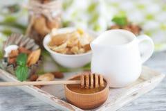 Miel en el cuenco, el muesli, las hojas de menta, las almendras y el tarro con leche en la bandeja de madera Fotografía de archivo libre de regalías