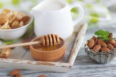 Miel en el cuenco, el muesli, las hojas de menta, las almendras y el tarro con leche en la bandeja de madera Imágenes de archivo libres de regalías