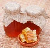 Miel en el tarro de cristal con la colmena de la abeja Foto de archivo libre de regalías