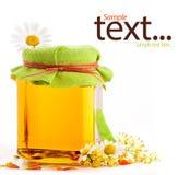 Miel en el tarro de cristal con las flores Fotos de archivo