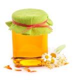 Miel en el tarro de cristal con las flores Imagen de archivo