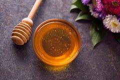 Miel en el tarro de cristal en la tabla Imágenes de archivo libres de regalías