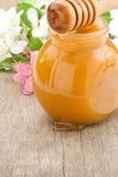Miel en el tarro y el palillo de cristal con las flores Foto de archivo libre de regalías