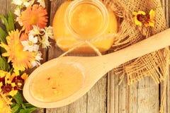 Miel en los tarros de cristal con el fondo de las flores Fotos de archivo