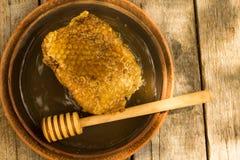 Miel en tarro con el cazo de la miel en fondo de madera Foto de archivo