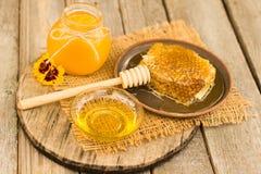 Miel en tarro con el cazo de la miel en fondo de madera Fotografía de archivo libre de regalías