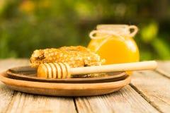 Miel en tarro con el cazo de la miel en fondo de madera Fotos de archivo libres de regalías
