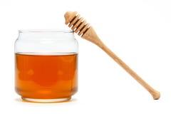 Miel en tarro con el cazo en fondo aislado Foto de archivo