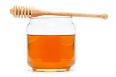 Miel en tarro con el cazo en fondo aislado Imagenes de archivo