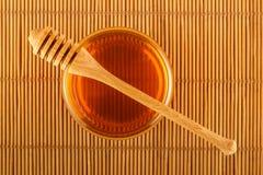 Miel en tarro con el cazo en la estera Imágenes de archivo libres de regalías