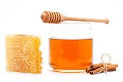 Miel en tarro con el cazo, panal, canela en fondo aislado Fotos de archivo