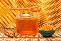 Miel en tarro con el cazo, panal, canela y fotografía de archivo