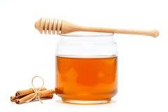 Miel en tarro con el cazo y canela en fondo aislado Fotografía de archivo