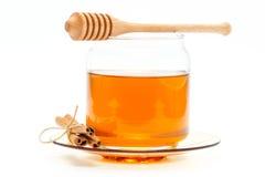 Miel en tarro con el cazo y canela en fondo aislado Imágenes de archivo libres de regalías