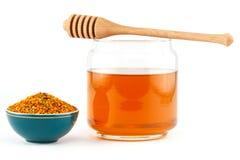 Miel en tarro con el cazo y polen en fondo aislado fotos de archivo
