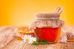 Miel en tarro con el panal y el drizzler de madera Fotos de archivo