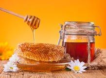 Miel en tarro con el panal y el drizzler de madera Foto de archivo