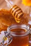 Miel en tarro con el panal y el drizzler de madera Imagen de archivo