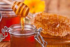 Miel en tarro con el panal y el drizzler de madera Fotografía de archivo