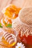 Miel en tarro con el panal y el drizzler de madera Fotografía de archivo libre de regalías
