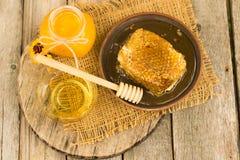 Miel en tarro con el panal y el fondo de madera Imágenes de archivo libres de regalías