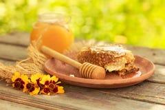 Miel en tarro con el panal y el fondo de madera Imagen de archivo libre de regalías