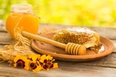 Miel en tarro con el panal y el fondo de madera Imagenes de archivo