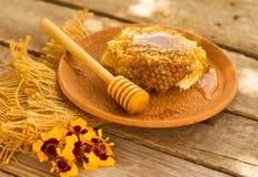 Miel en tarro con el panal y el fondo de madera Foto de archivo