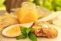 Miel en tarro con el panal y el fondo de madera Fotos de archivo