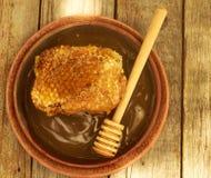 Miel en tarro con el panal y el fondo de madera Imagen de archivo