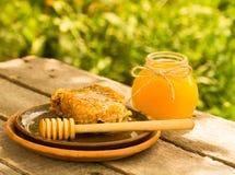 Miel en tarro con el panal y el fondo de madera Fotografía de archivo