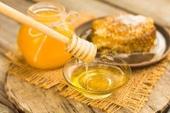 Miel en tarro con el panal y el fondo de madera Fotografía de archivo libre de regalías