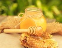 Miel en tarro con el panal y el fondo de madera Foto de archivo libre de regalías