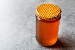 Miel en tarro con la tapa Copie el espacio Imagen de archivo libre de regalías