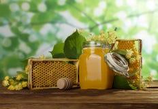 Miel en tarro con la tapa, panal en la tabla, primer Imagen de archivo