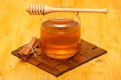 Miel en tarro con las barras del cazo y del canela foto de archivo libre de regalías