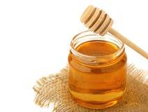 Miel en tarro con una cuchara de madera aislada en el fondo blanco Imágenes de archivo libres de regalías