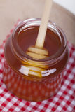 Miel en tarro en un fondo de madera Imágenes de archivo libres de regalías