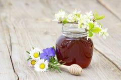 Miel en tarro, flores y cazo de la miel Imágenes de archivo libres de regalías