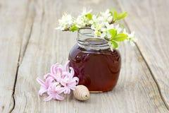 Miel en tarro, flores y cazo de la miel Fotografía de archivo libre de regalías