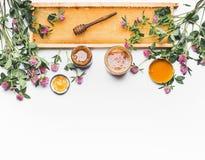 Miel en tarros con el cazo, el marco del panal y las flores salvajes en el fondo blanco, visión superior Alimento sano Foto de archivo