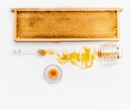Miel en tarros con el cazo, el marco del panal y las flores salvajes en el fondo blanco, visión superior Alimento sano Fotografía de archivo libre de regalías