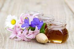 Miel en tarros, flores y cazo de la miel Fotografía de archivo