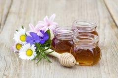 Miel en tarros, flores y cazo de la miel Imagen de archivo libre de regalías