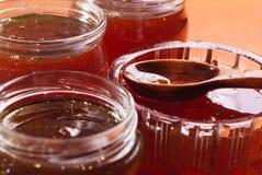 Miel en tarros, una cuchara de madera con la miel Fotos de archivo