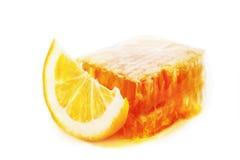 Miel en un panal al lado de una rebanada de limón aislada en blanco Imágenes de archivo libres de regalías