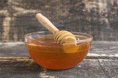 Miel en un tarro con la cuchara de la miel en una tabla rústica de madera del vintage Fotografía de archivo libre de regalías