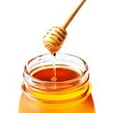 Miel en un tarro de cristal con el cazo de la miel aislado en blanco Foto de archivo