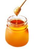 Miel en un tarro de cristal con el cazo de la miel aislado en el backgr blanco Imagen de archivo